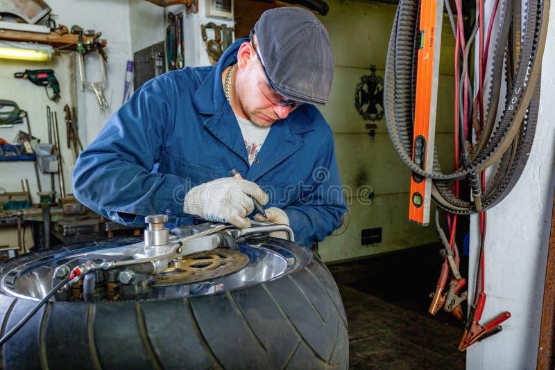 Man repairing motorcycle tire with repair kit, Tire plug repair kit for tubeless tires. The man repairing motorcycle tire with repair kit, Tire plug repair kit stock photos