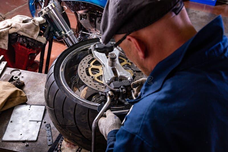 Man repairing motorcycle tire with repair kit, Tire plug repair kit for tubeless tires. The man repairing motorcycle tire with repair kit, Tire plug repair kit royalty free stock images