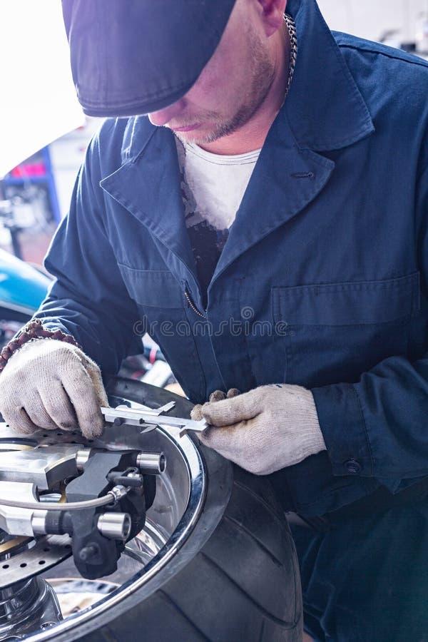 Man repairing motorcycle tire with repair kit, Tire plug repair kit for tubeless tires. The man repairing motorcycle tire with repair kit, Tire plug repair kit stock photo