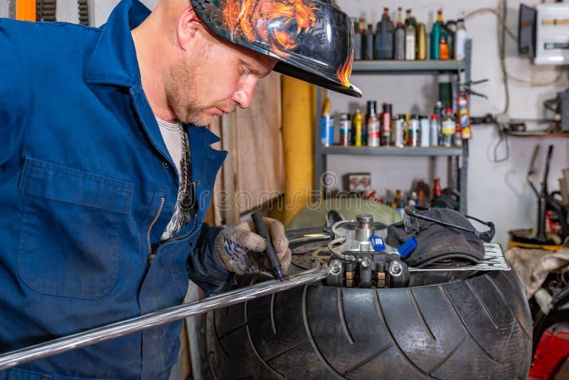 Man repairing motorcycle tire with repair kit, Tire plug repair kit for tubeless tires. The man repairing motorcycle tire with repair kit, Tire plug repair kit stock image
