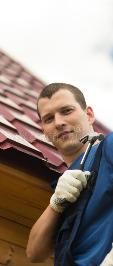 Man repairing the roof holds a hammer in his hand on the background of the roof of the house royalty free stock photos