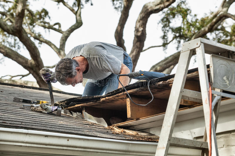 Man Repairing Rotten Leaking Roof. Close up view of man using crowbar and saw to remove rotten wood from leaky roof decking. After removing fascia boards he has stock images