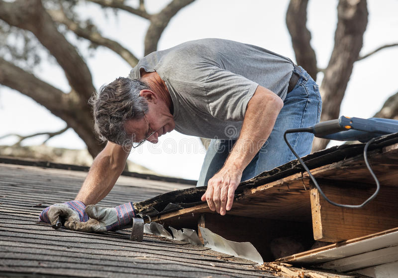 Man Repairing Rotten Leaking Roof. Close up view of man using crowbar and saw to remove rotten wood from leaky roof decking. After removing fascia boards he has royalty free stock photos