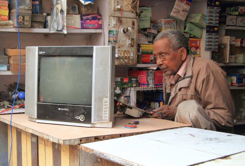Man is repairing tv in repair shop royalty free stock photography