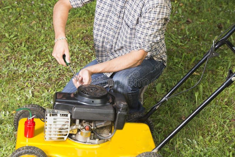 Man repairing yellow lawn mower stock images