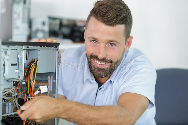 Man repairman trying to fix pc. Man repairman is trying to fix a pc royalty free stock photos
