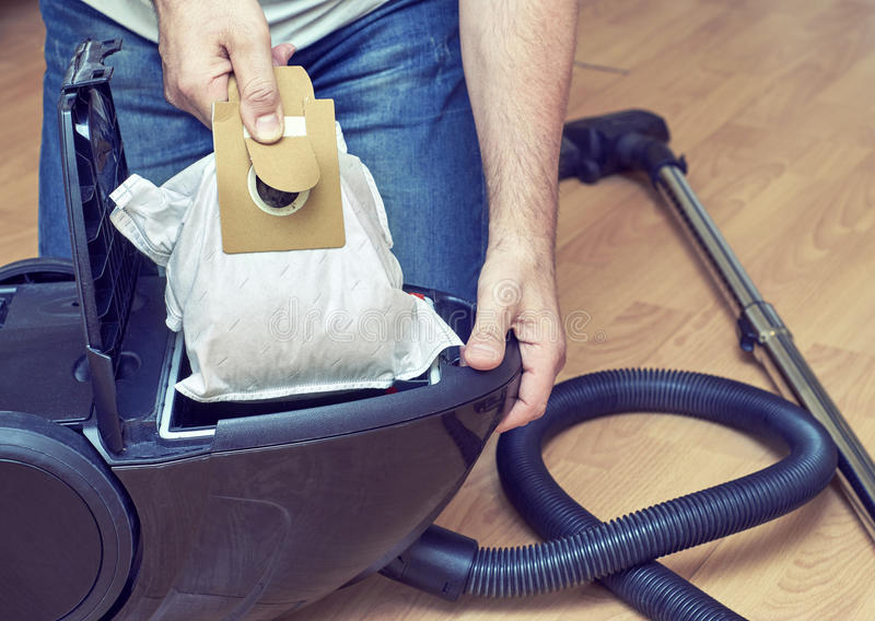 Man replacing a dust bag in vacuum cleaner stock photos