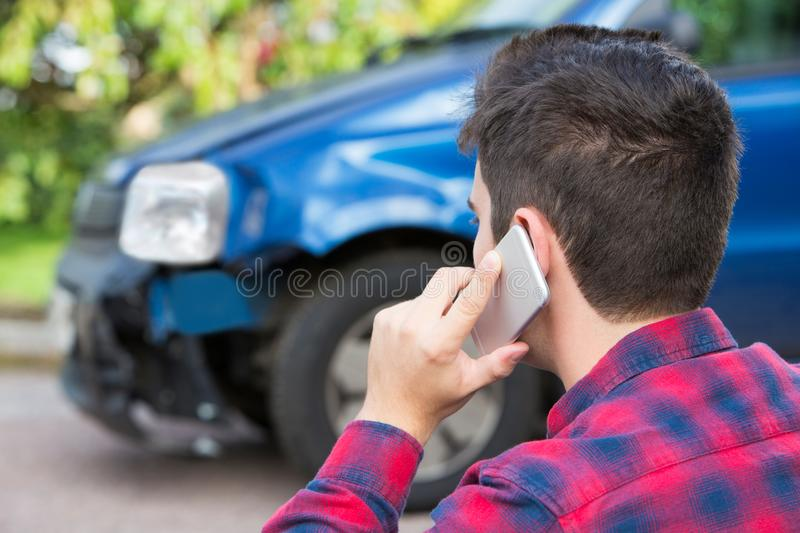Man Reporting Car Crash On Mobile Phone royalty free stock photography
