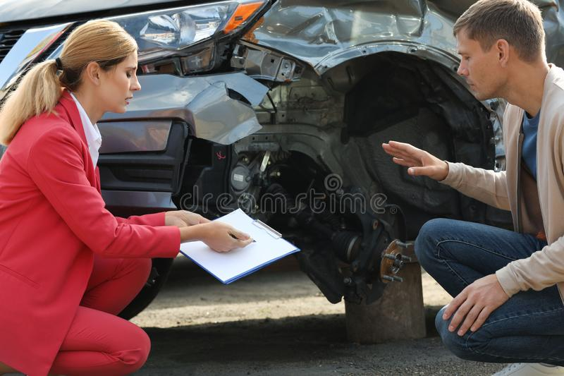 Man reporting and insurance agent filling claim form. Near broken car outdoors royalty free stock photo