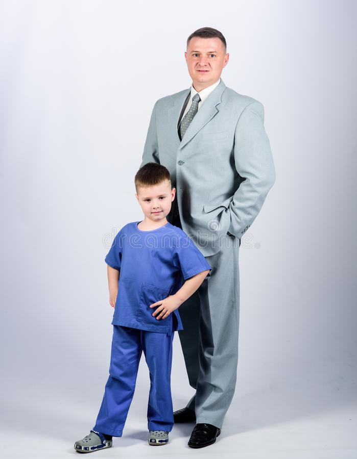 Man respectable businessman and little kid doctor uniform. Doctor respectable career. Dad boss. Father and cute small. Son. Child care development upbringing stock photography