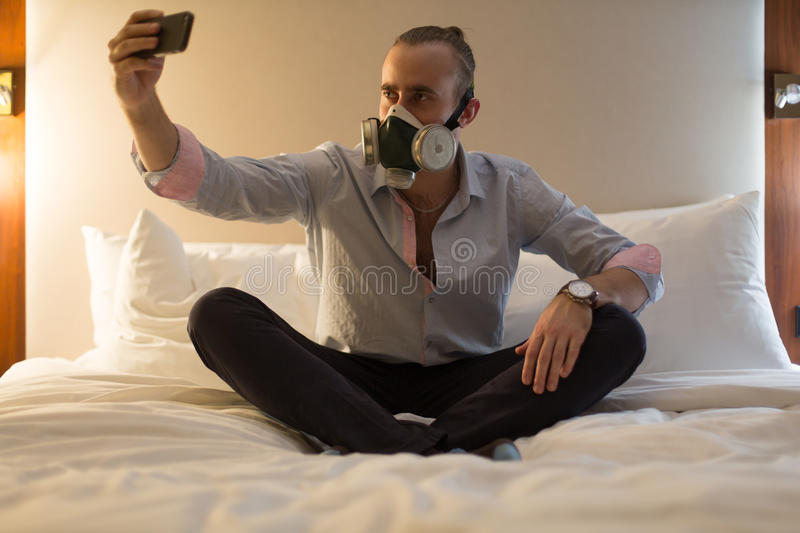 Man in respirator on the bed royalty free stock image
