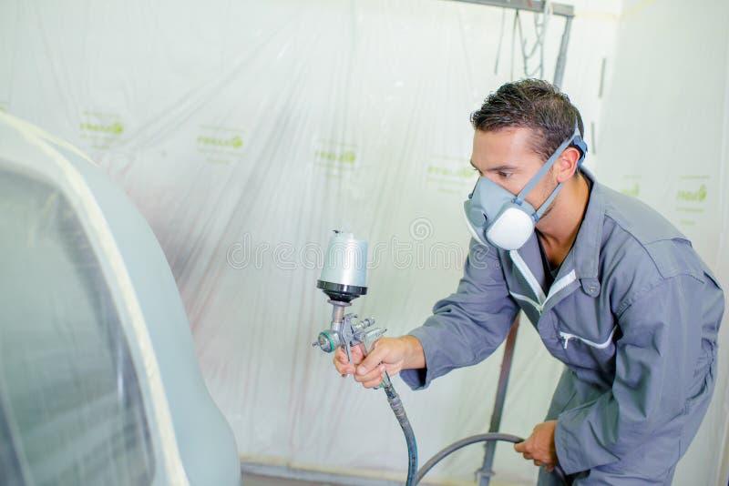 Man respraying car panel. Airbrush stock photography