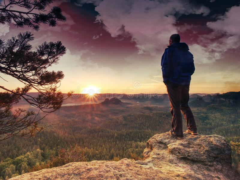 Man rest on mountain peak in background hills and clouds stock photography