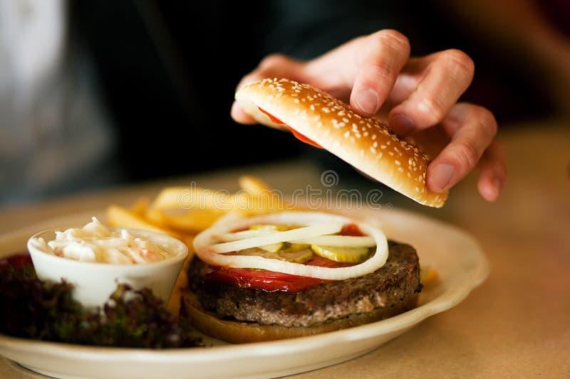 Download Man In Restaurant Eating Hamburger Stock Image - Image: 13179055