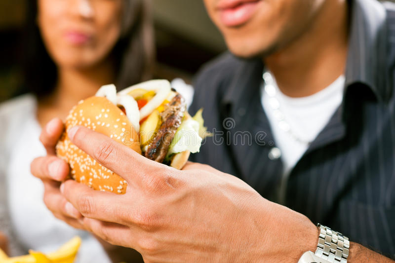 Man in a restaurant eating hamburger royalty free stock photography