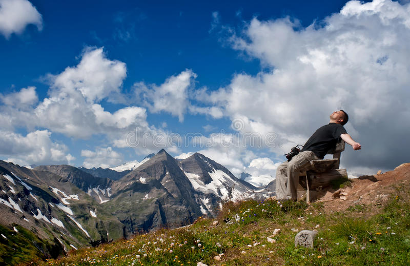 Man resting on a bench and looking at the sky. royalty free stock photography