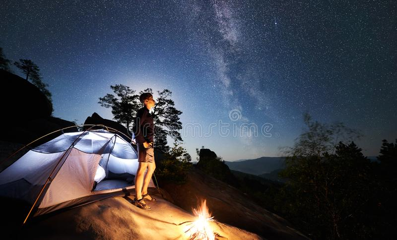 Man resting beside camp, bonfire and tourist tent at night. Young hiker man having a rest on rocky mountain top beside camp, campfire and illuminated tourist stock photos