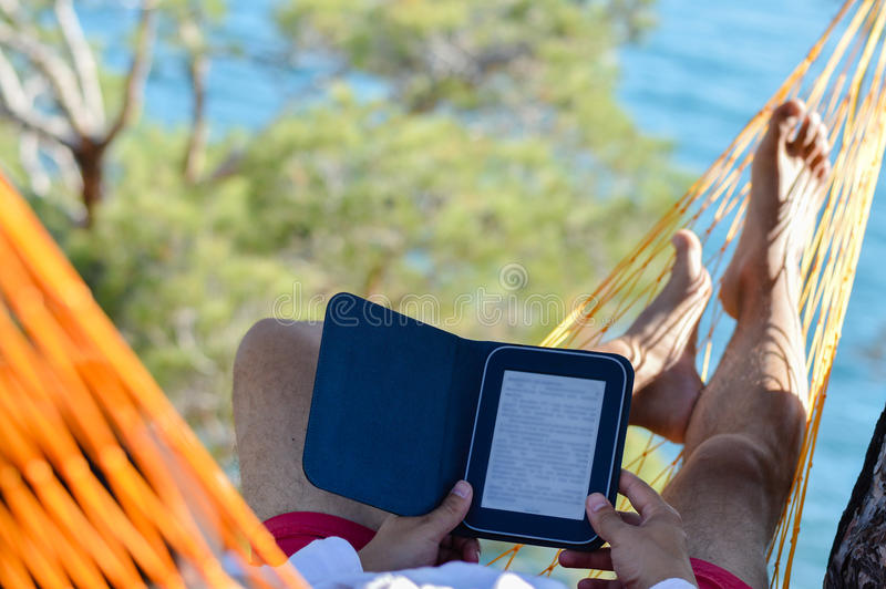 Man resting in hammock on seashore and reading ebook. Man relaxing in orange hammock on seashore and reading ebook on summer sea outdoors background stock images