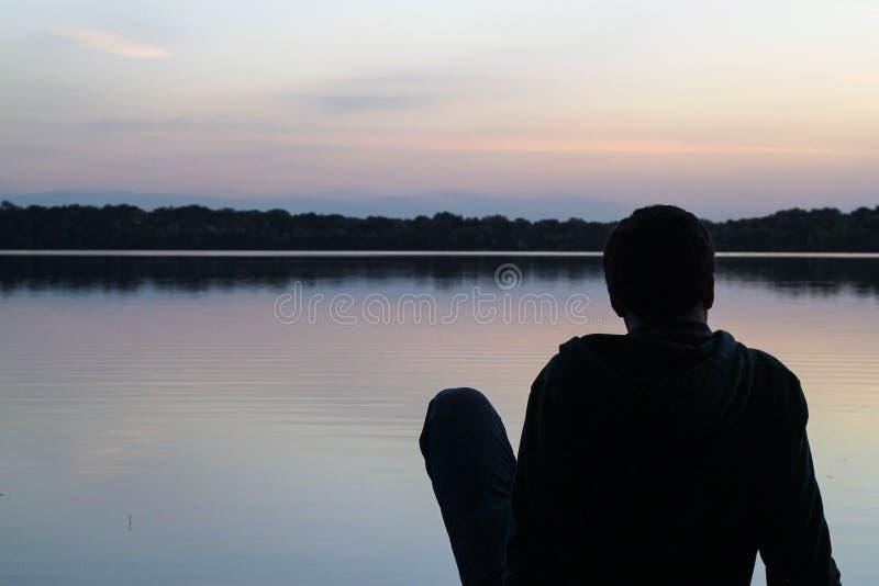Man resting beside lake royalty free stock photos