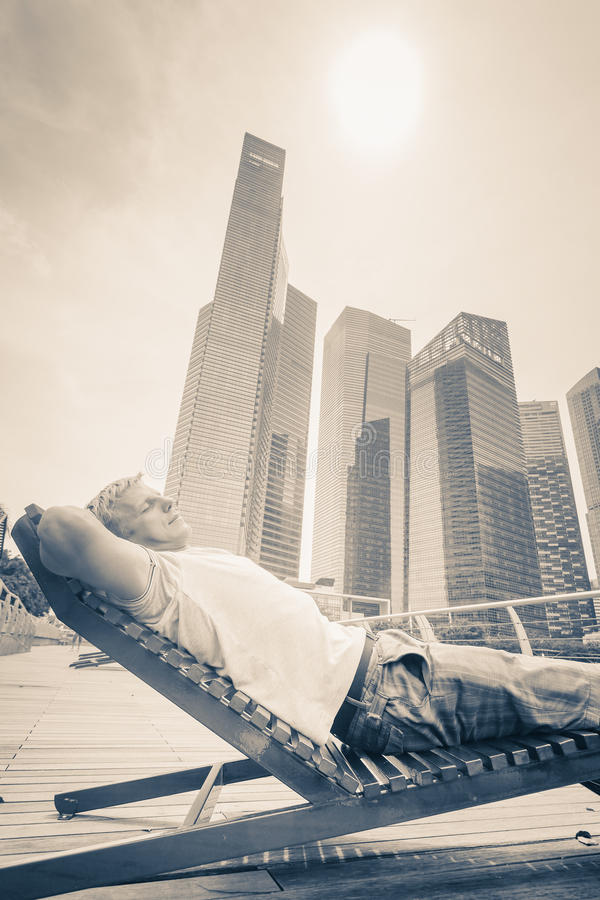 Man resting near the waterfront in Singapore in front of business buildings royalty free stock image