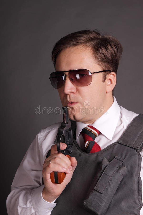 The man with a revolver. The man in a bullet-proof vest with a revolver on a grey background royalty free stock image