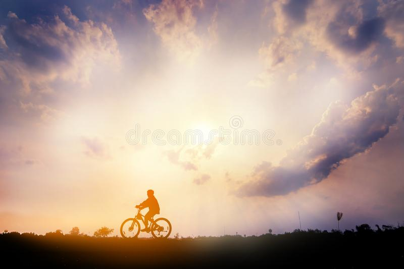A man Ride on bike on the road with beautiful colorful sky. Silhouette of cyclist ride bicycle on sunset background. A man Ride on bike on the road with stock photography