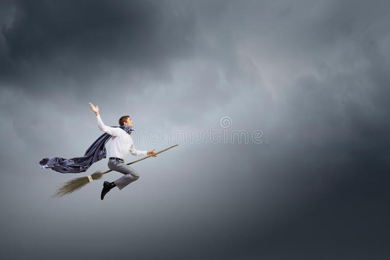 Man ride broom. Young businessman flying on broom high in sky stock photo