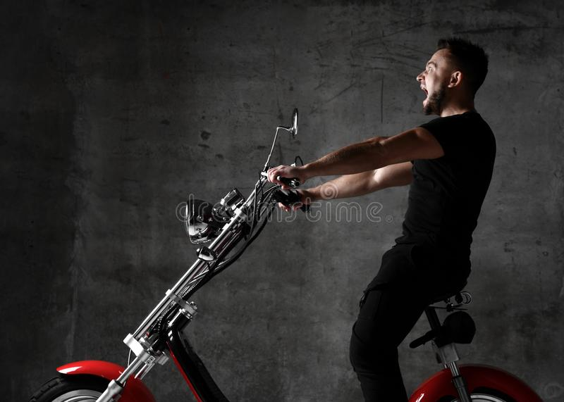 Man ride new electric car motorcycle bicycle scooter in black cloth shout out loud on concrete wall royalty free stock images