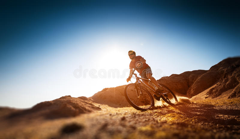 Man rides bicycle. In the dry desert terrain stock photo