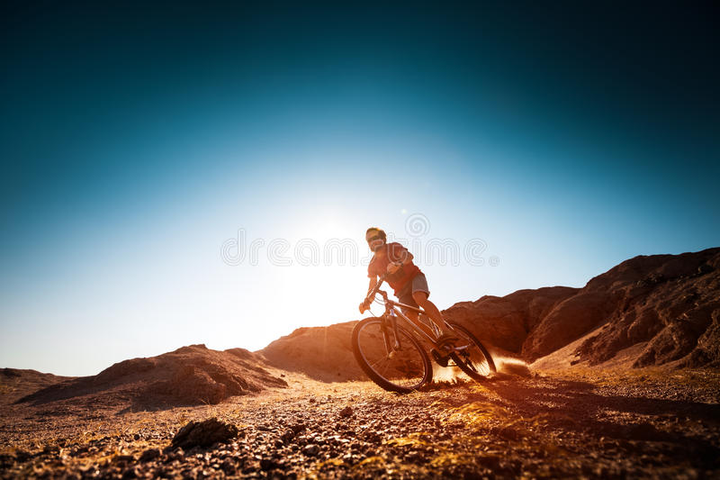 Man rides bicycle. In the dry desert terrain stock image