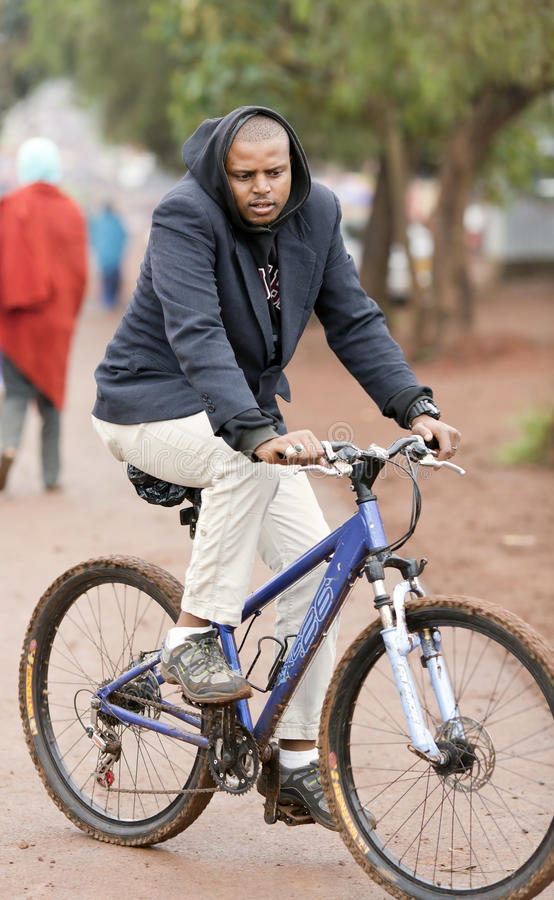 A man rides a bicycle on the street in Arusha. AFRICA, TANZANIA, MAY, 09, 2016 - A man rides a bicycle on the street in Arusha. Arusha is located below Mount royalty free stock images