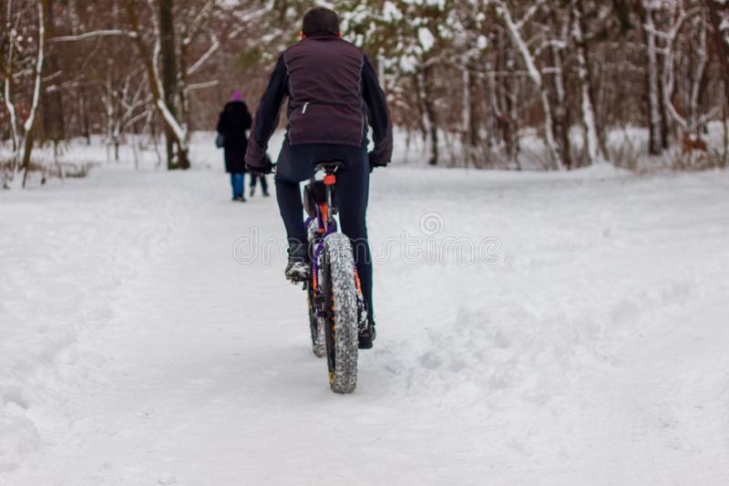 A man rides a bicycle in the winter in the snow. royalty free stock photo