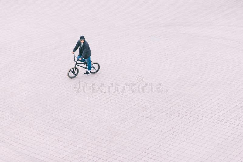 Man rides a BMX bike on a square, a view from above. BMX concept royalty free stock images