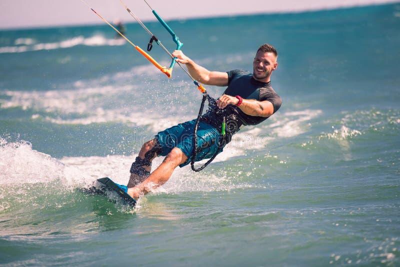 Man rides on kite on waves stock photos
