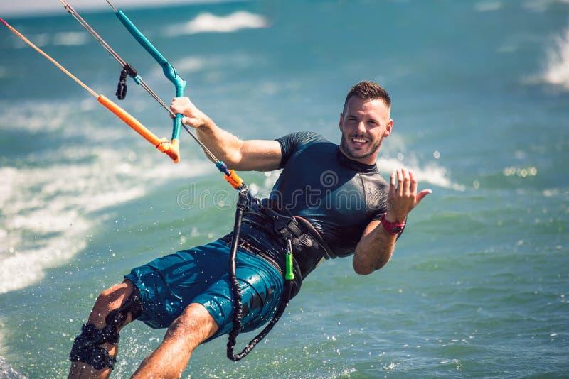 Man rides on kite on waves royalty free stock photos