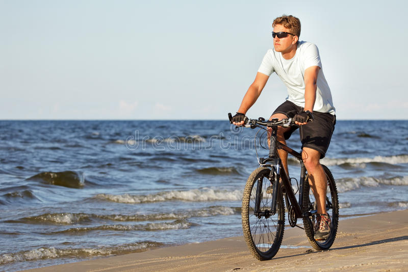 Man Riding Bicycle In Beach Stock Images