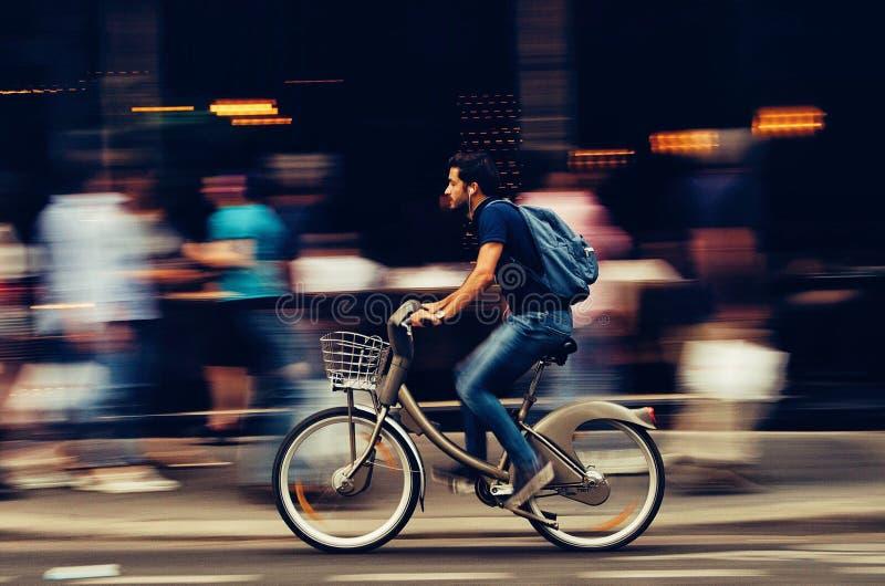 Man Riding Bicycle on City Street royalty free stock photos