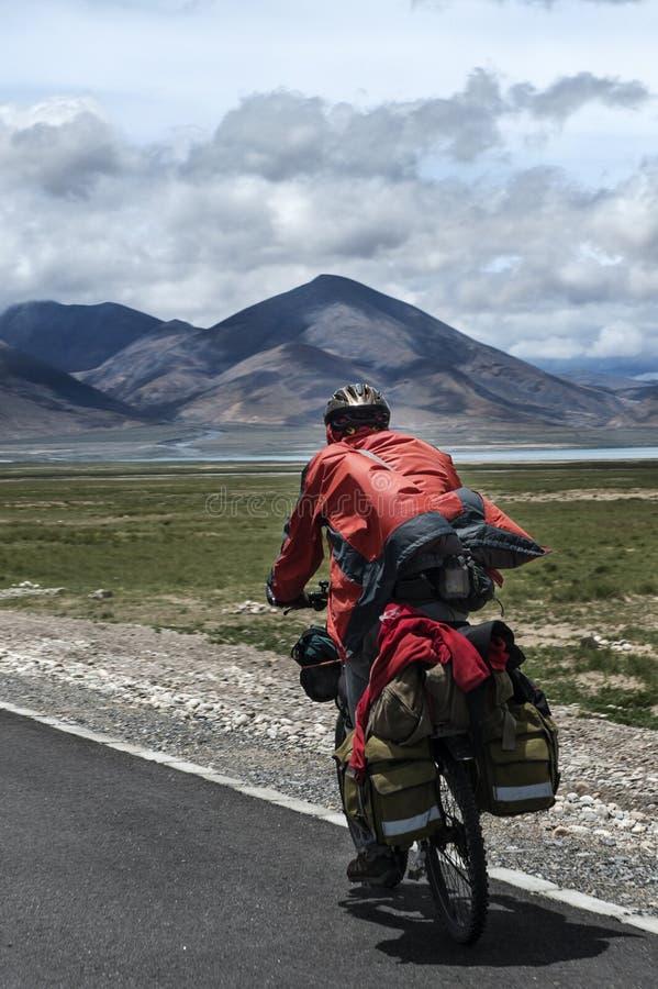 Man riding bicycle in Tibetan stock images