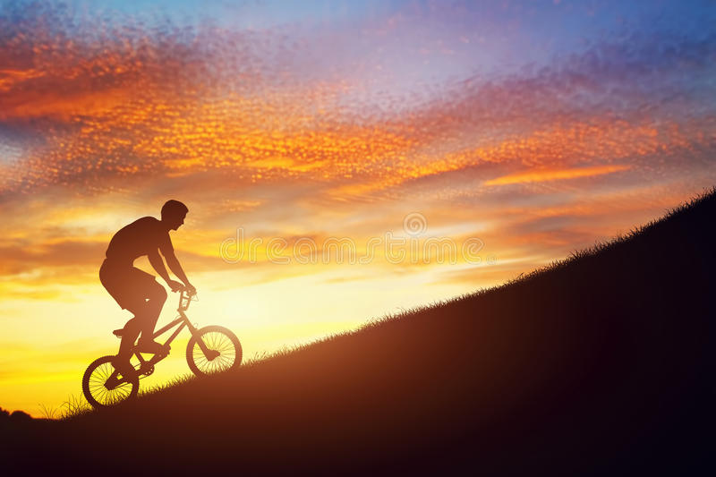 Man riding a bmx bike uphill against sunset sky. Strength, challenge. Man riding a bmx bike uphill against sunset sky. Active lifestyle, motivation, strength royalty free illustration