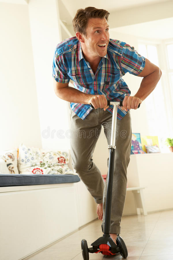 Download Man Riding Child's Scooter Indoors Stock Photo - Image: 26104986