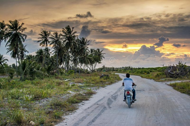 The man riding cycle on the road during sunset time at the tropical island stock image