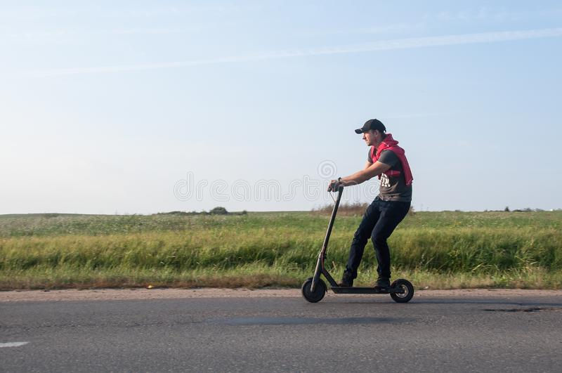 Man riding an electric scooter royalty free stock images