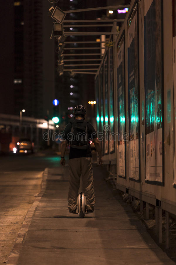 Man riding electric unicycle at night royalty free stock image