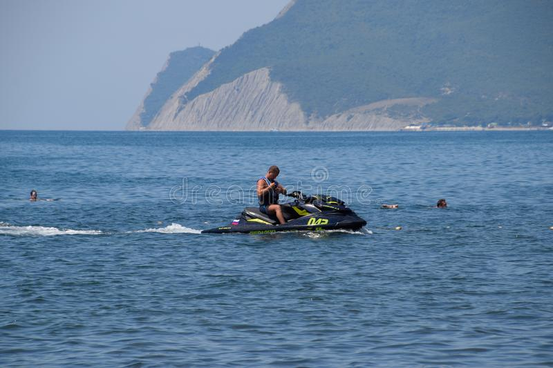 A man is riding a hydrocycle. Novorossiysk, Russia - August 06, 2018: A man is riding a hydrocycle. Sea beach of the Broad Beam near the city of Novorossiysk royalty free stock photography