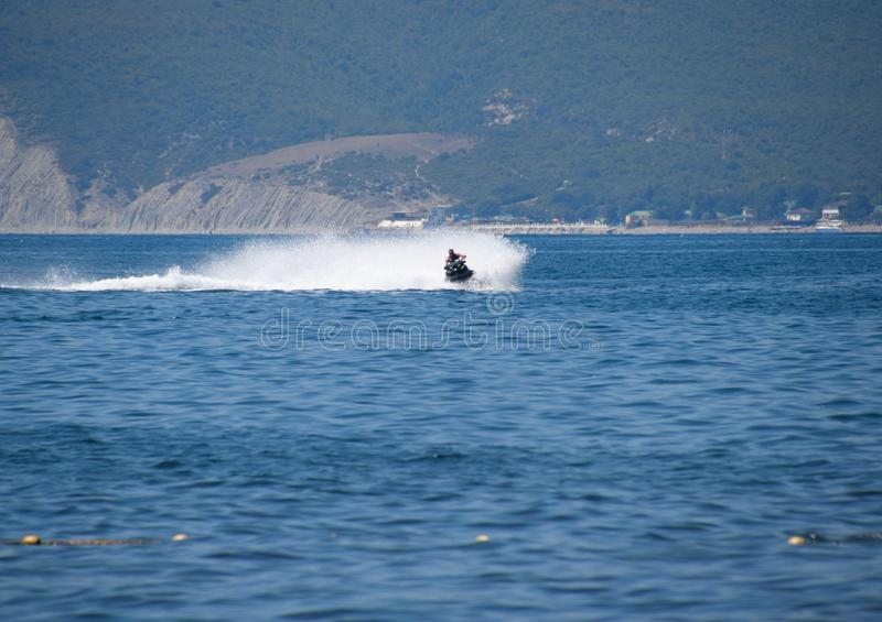 A man is riding a hydrocycle. Novorossiysk, Russia - August 06, 2018: A man is riding a hydrocycle. Sea beach of the Broad Beam near the city of Novorossiysk royalty free stock images