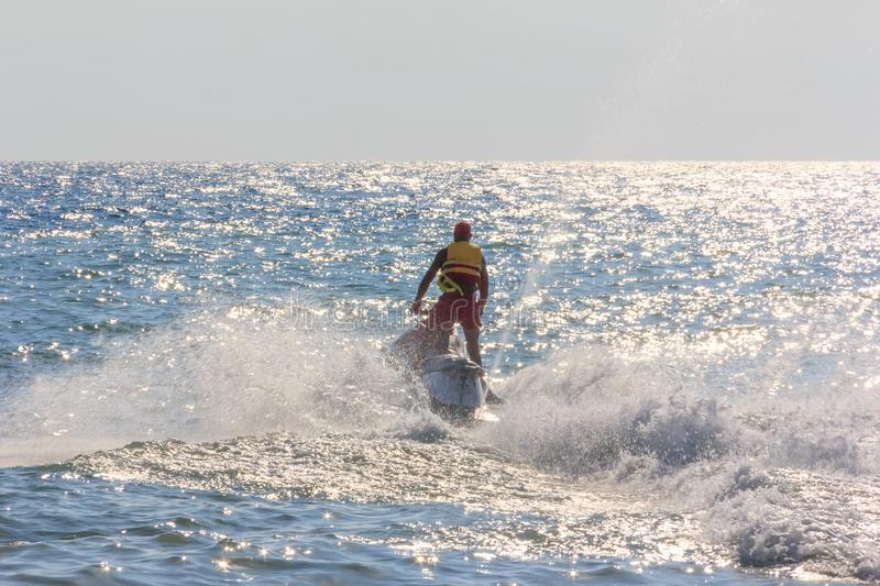 Man riding a hydrocycle in the sea. Young man riding a hydrocycle in the sea royalty free stock images