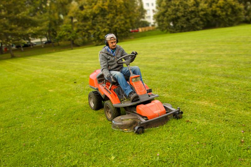 Man riding lawn mower stock photography