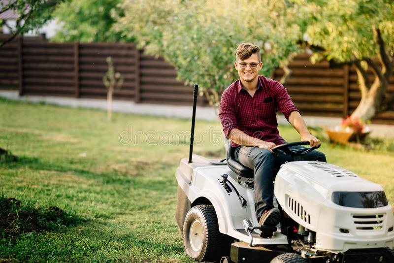 Man riding a lawnmower and doing landscaping works. Smiling man riding a lawnmower and doing landscaping works royalty free stock photo