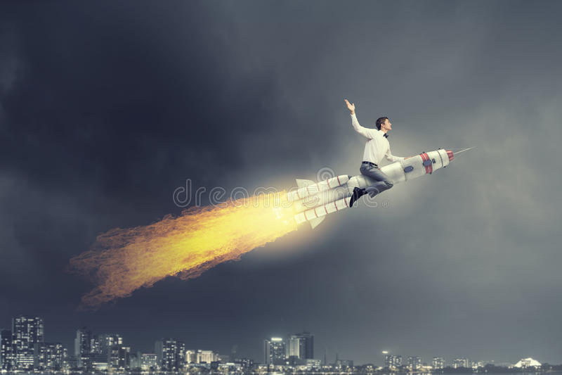 Man riding missile . Mixed media. Young businessman flying in sky on space rocket royalty free stock photos