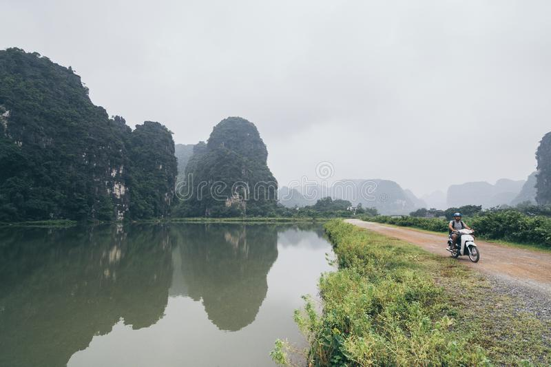 Man riding motorcycle among limestone mountains in Ninh Binh province, Vietnam. Cloudy day, reflection in water, motorbike, scooter, rental, stand, lake royalty free stock image